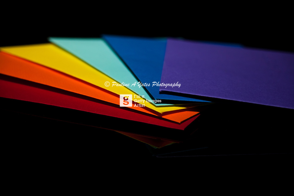 A Fan of rainbow coloured envelopes on a black glass surface