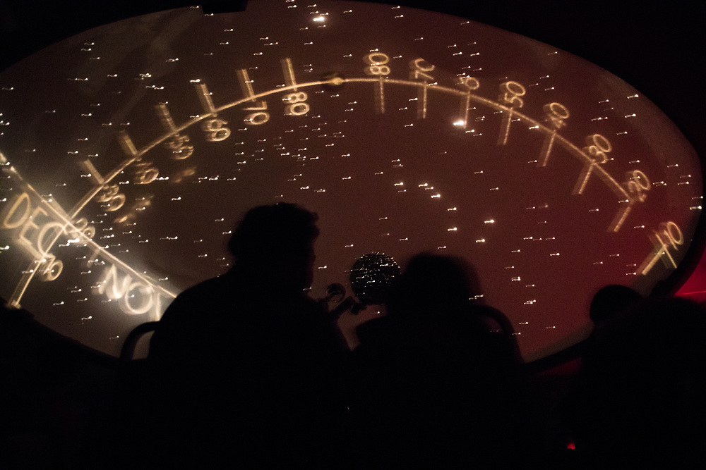 """Participants listen to Aidan Temperino '21 of Plymouth, N.H., and Maggie Phelan '20 of Lewiston, Maine, present inside the Ladd Planetarium in the Carnegie Science Hall during the Bates College Astronomy Night Extravaganza on April 2, 2018. """"Our presentation focused on the changing of the sky as each season changes here, so one of the big things we wanted to have people walk away with was learning what causes the seasons here in Lewiston cause we are fortunate to have all four seasons,"""" says Temperino.<br /> <br /> """"The line going vertically across is the meridian and that one shows the latitude in the<br /> sky which also corresponds to our latitude on earth and the other one was the ecliptic which is<br /> the suns path throughout the year during each month. So at the peak of each month that would indicate noon and that would show us how high the sun is in the sky,"""" says Phelan."""