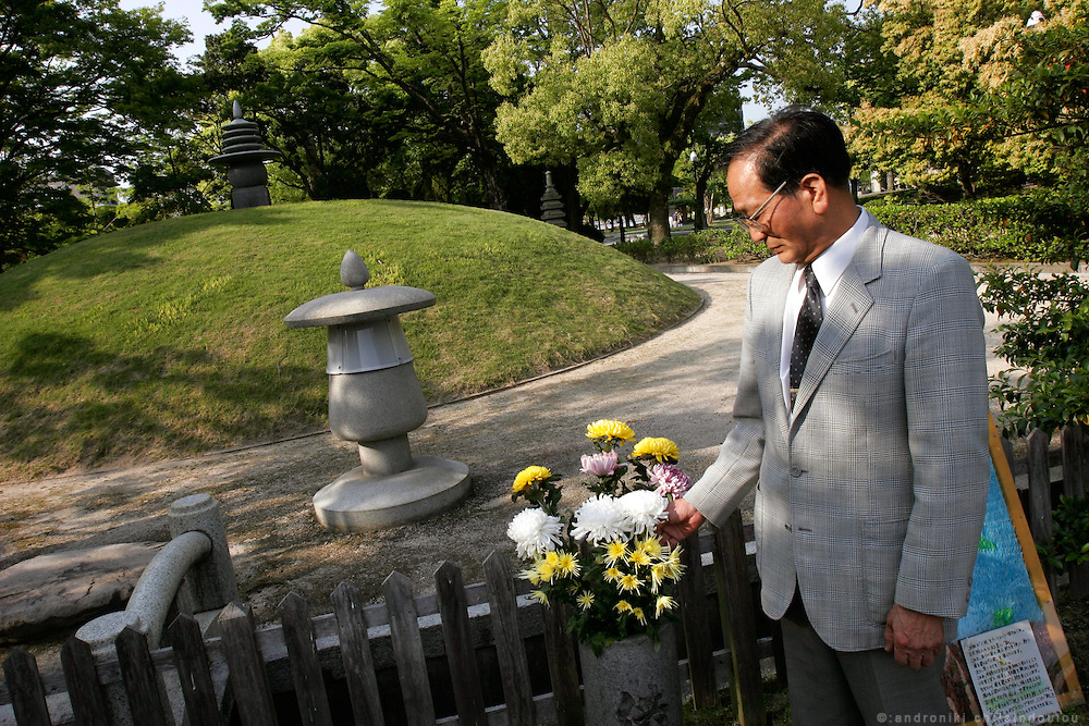 HITOSHI TAKAYAMA Hiroshima A-bomb survivor, in front of the tomb for unknown victims at the Peace Memorial Park. He was 15 years old and training to work at the Nippon Express Company automobile garage in Minami-machi when the bomb fell. He immediately ran inside a building which protected him from immediate injury, but 16 years later he developed cancer on his hip and back.  He remembers the scenes of horror and the suffering of dying people he saw around him.  He lifts his shirt to show where much of the muscle from his back was removed in the cancer operation. I don't mind showing people my injuries if it teaches them about what happened.