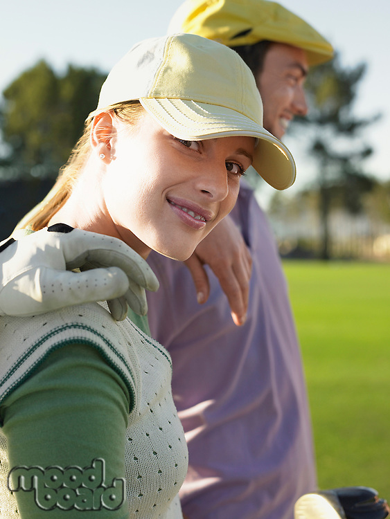 Two young golfers on court focus on woman