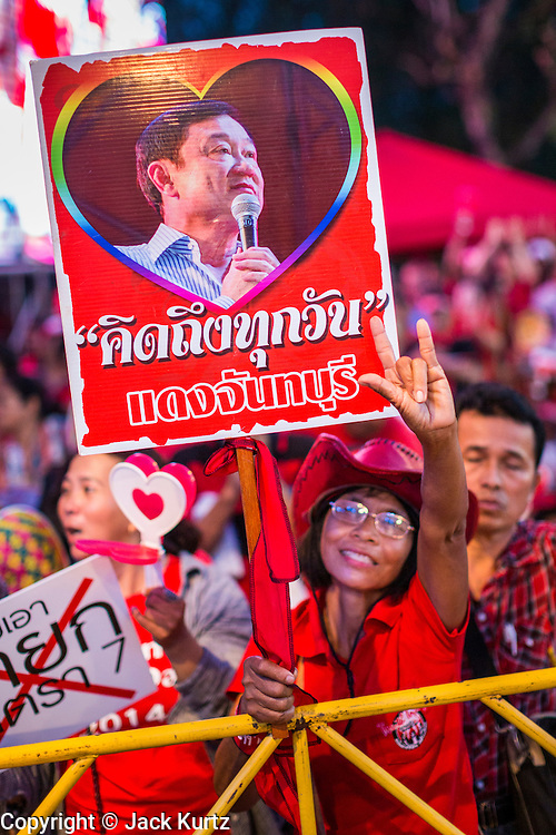 10 MAY 2014 - BANGKOK, THAILAND: A Red Shirt supporter with a photo of ousted and exiled former Prime Minister Thaksin Shinawatra cheers for ousted Prime Minister Yingluck Shinawatra (Yingluck is Thaksin's sister) at a rally in Bangkok. Thousands of Thai Red Shirts, members of the United Front for Democracy Against Dictatorship (UDD), members of the ruling Pheu Thai party and supporters of the government of ousted Prime Minister Yingluck Shinawatra are rallying on Aksa Road in the Bangkok suburbs. The government was ousted by a court ruling earlier in the week that deposed Yingluck because the judges said she acted unconstitutionally in a personnel matter early in her administration. Thailand now has no functioning government. Red Shirt leaders said at the rally Saturday that any attempt to impose an unelected government on Thailand could spark a civil war. This is the third consecutive popularly elected UDD supported government ousted by the courts in less than 10 years.    PHOTO BY JACK KURTZ