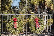 A wrought iron garden gate of a historic home decorated with Christmas wreaths on Water Street in Charleston, SC.