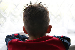 Young boy looking out of window,