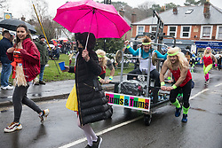 Windlesham, UK. 26 December, 2019. Competitors in high spirits despite heavy rain take part in the annual fancy dress Windlesham Boxing Day Pram Race charity event along a 3.5-mile course through Windlesham village with stops at local pubs along the route.