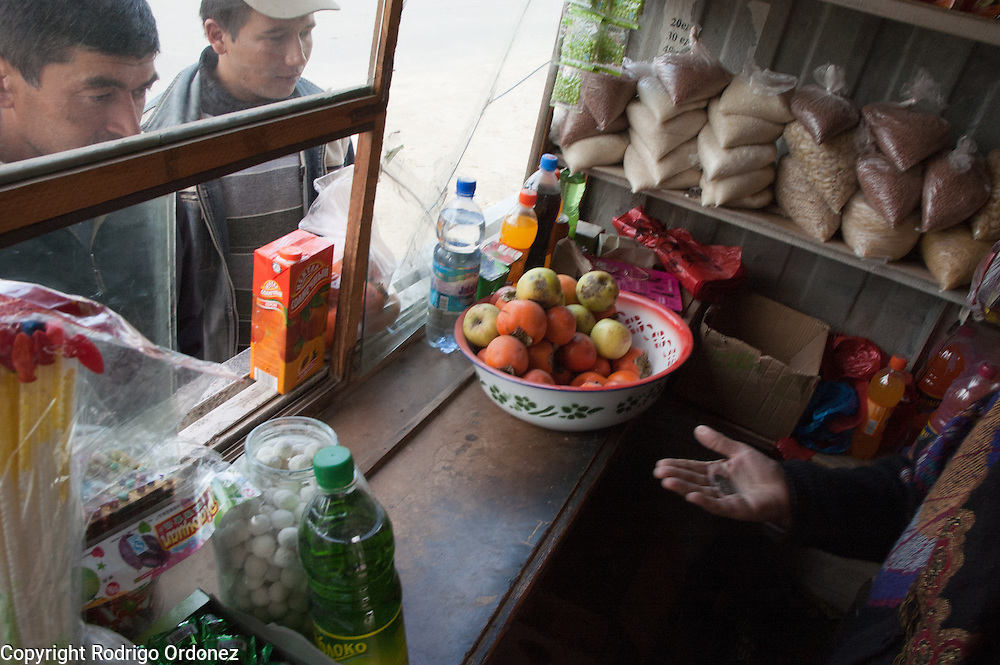 Matlubahan Umarjanova, 60, gives change to a customer at her shop in Osh (Kyrgyzstan). With equipment and materials provided by Save the Children, she reopened her business, a kiosk selling groceries and common household items.