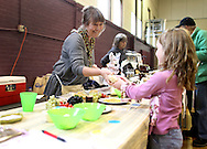 Barbara Grant (from left) of Springville sells a package of Acoustic Farms cheese to Elizabeth Barns, 6, of Cedar Rapids during the Indoor Winter Farmers Market at the First Street Community Center at 221 First Street NE in Mount Vernon on Saturday, April 16, 2011.