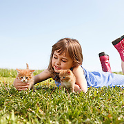 Smiling girl 4-6 wearing dress and cowboy boots lying on grass with two kittens