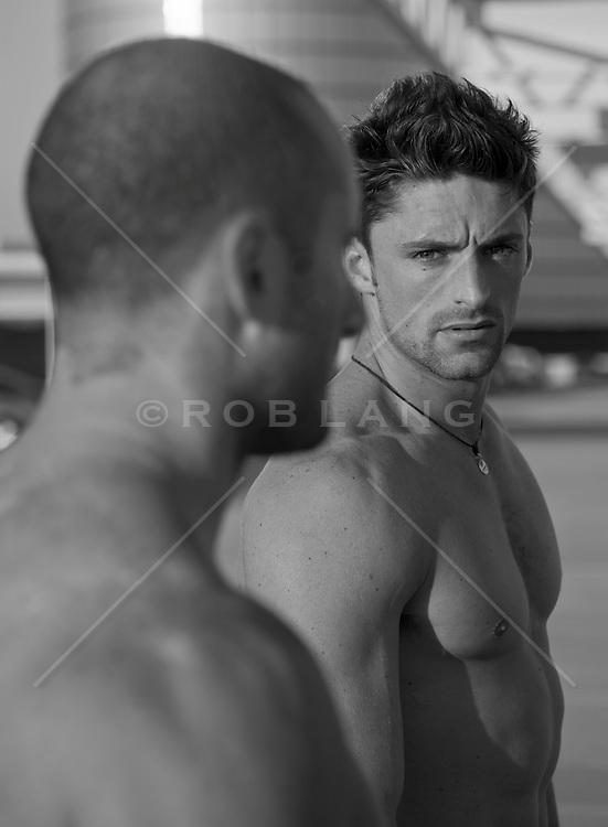 Shirtless man looking back at another man, (b&W)