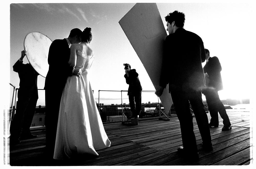 Vädret och utsikten kan knappast bli mer filmiskt än så här. Med utsikt över hela Manhattan plåtas brudparet av den stressade fotografen som försöker få så många olika vinklar under de få minuter som ljuset är perfekt i solnedgången..Joby Harold and Tory Tunnell's wedding in New York City..Photographer: Chris Maluszynski /MOMENT