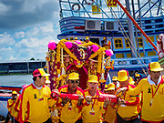 "02 JUNE 2017 - SAMUT SAKHON, THAILAND: The team carrying the City Pillar Shrine take the Shrine off the boat during the procession for the shrine. The Chaopho Lak Mueang Procession (City Pillar Shrine Procession) is a religious festival that takes place in June in front of city hall in Samut Sakhon. The ""Chaopho Lak Mueang"" is  placed on a fishing boat and taken across the Tha Chin River from Talat Maha Chai to Tha Chalom in the area of Wat Suwannaram and then paraded through the community before returning to the temple in Samut Sakhon. Samut Sakhon is always known by its historic name of Mahachai.      PHOTO BY JACK KURTZ"