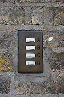 Old apartment buzzer buttons on brick wall in Dublin Ireland