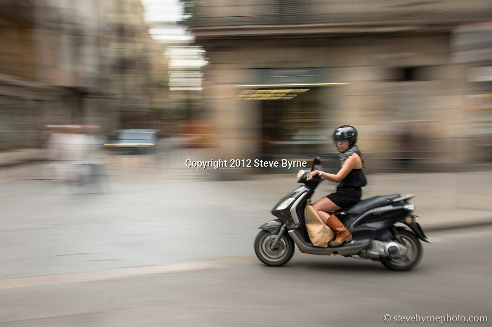 A woman commuting via scooter weaves her way through the narrow streets of the Born District of Barcelona.