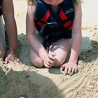 Young girl studies ping pong balls used to represent eggs of the threatened Green Sea Turtles.