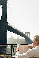 Man reading newspaper by Brooklyn Bridge