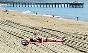 Woman on the Sand Reading a Book by Balboa Pier in Newport Beach California