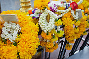 25 MARCH 2010 - BANGKOK, THAILAND: Flower garlands left as offerings at the Erawan Shrine in Bangkok. The Erawan Shrine (Thai: San Phra Phrom) is a Hindu shrine in Bangkok, Thailand that houses a statue of Phra Phrom, the Thai representation of the Hindu creation god Brahma. The Erawan Shrine was built in 1956 as part of the government-owned Erawan Hotel to eliminate the bad karma believed caused by laying the foundations on the wrong date. The hotel's construction was delayed by a series of mishaps, including cost overruns, injuries to laborers, and the loss of a shipload of Italian marble intended for the building. Furthermore, the Ratchaprasong Intersection had once been used to put criminals on public display. An astrologer advised building the shrine to counter the negative influences. The Brahma statue was designed and built by the Department of Fine Arts and enshrined on 9 November 1956. The hotel's construction thereafter proceeded without further incident.      PHOTO BY JACK KURTZ