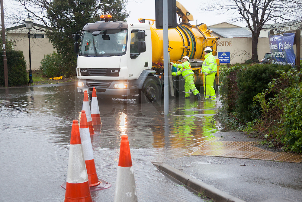 © Licensed to London News Pictures. 01/01/2014. Portsmouth, Hampshire, UK. Workers trying to unblock drains following flooding in Portsmouth, Hampshire. The Eastern Road flooded due to strong winds and the high tide. Photo credit : Rob Arnold/LNP