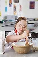 Girl (10-12) with Down syndrome mixing contents in bowl