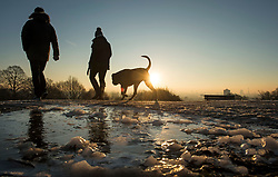 © Licensed to London News Pictures. 12/12/2017. London, UK. A couple walk their dog in freezing conditions on Hampstead Heath in north London on a bright, sunny morning. Temperatures across the the UK dipped overnight with some regions expected to drop to -13C (9F). Photo credit: Ben Cawthra/LNP