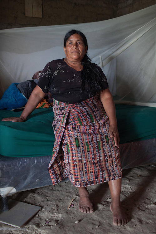 Patrocinia Sanchez Chen, 57, survivor from Rio Negro, sits on her bed. She hopes the Forensic Anthropology Foundation of Guatemala (FAFG) identifies and returns family members killed or abducted during the May 14, 1982, Los Encuentros Massacre and quite likely exhumed in 2012 from grave XV at the UN's CREOMPAZ training center, formerly Coban's Military Zone 21. During the massacre, Guatemalan soldiers and civil patrolmen killed 79 community members from Rio Negro who were hiding here after the previous two massacres of February and March of the same year. Eyewitnesses assured that at least 15 other community members were abducted in a helicopter. As of May 2016, CREOMPAZ's grave XV has rendered positive DNA matches of the remains of two victims abducted in the helicopter on such day. Patrocinia is hoping to find and bury the remains of her following siblings lost during the massacre: Andrea Sanchez Sic (10), Angela Sanchez Sic (6) and Francisco Sanchez Sic (4). She doesn't know if they were killed in Los Encuentros or taken by Helicopter. Patrocinia lives in Pacux, the resettlement village outside Rabinal where the former Achi Mayan residents of Rio Negro were forcibly relocated after the massacres and destruction of their village and dozens more due to the flooding of the Chixoy river basin and construction of the Chixoy Hydro-electric project. Pacux, Rabinal, Baja Verapaz, Guatemala. May 20, 2016.