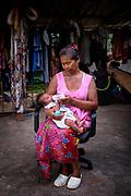 Siri, a Thai woman farmer, cares for her newborn grandson in rural Thailand. PHOTO BY LEE CRAKER