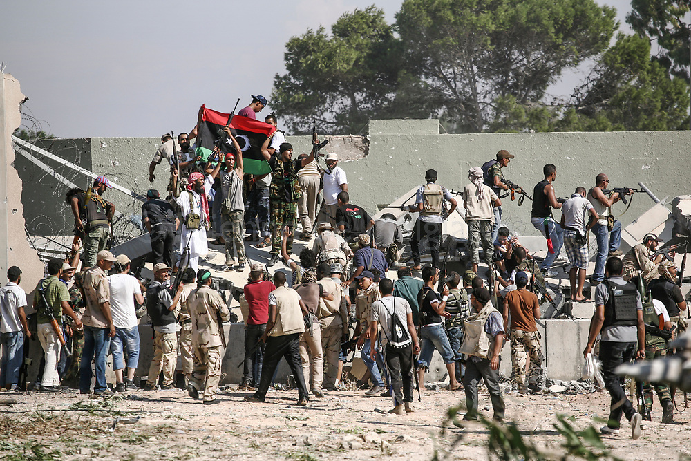 Libyan rebels launch an attack at Bab Al Aziziya,  Gadhafi's headquarter in Tripoli. Amid fierce gunfire, a Caterpillar opened a breach in the outer wall for the rebels to swarm the fortified compound.<br /> 23 August 2011.