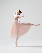 Classical female ballet dancer, Alexandra Gallagher, in a pink romantic dress in the photo studio on a light grey background. Photograph taken in New York City by photographer Rachel Neville.