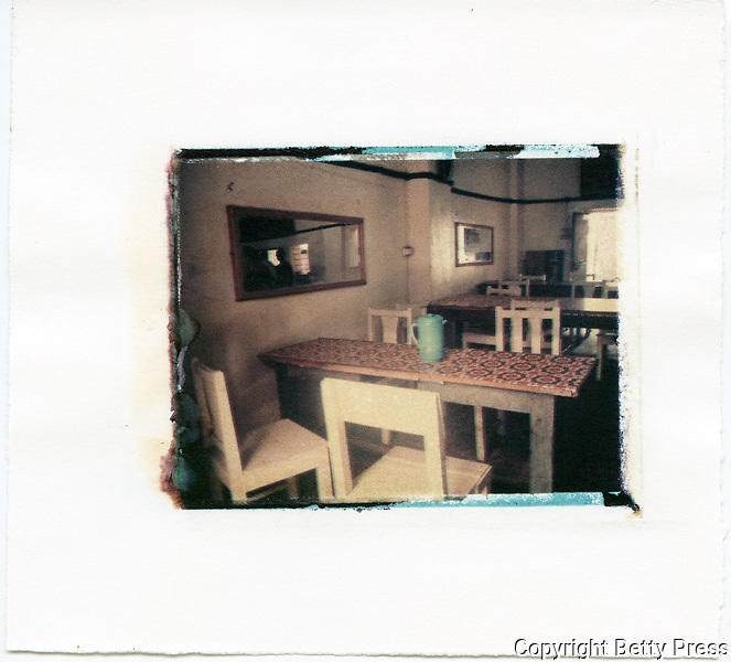 Blue pitcher sits on a table after the lunch hour in a typical small restaurant.<br />