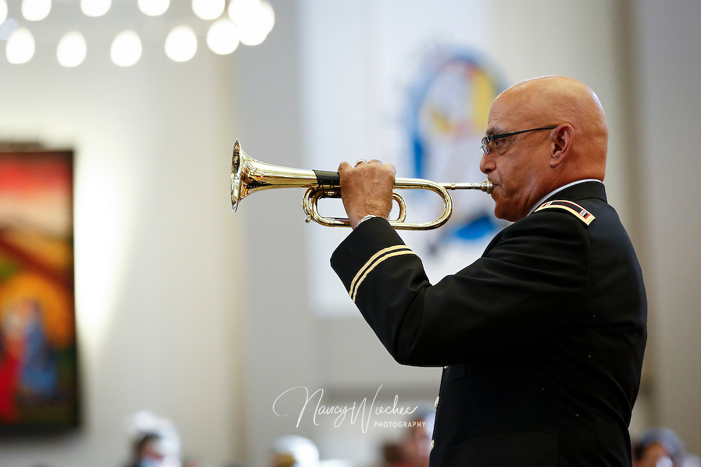"A serviceman plays the bugle call ""Taps"" prior to the celebration of the sixth annual Red, White and Blue Mass at St. Thomas Aquinas Church in Avondale, Ariz., Nov. 6. The Diocese of Phoenix marked the occasion to honor active and retired service men and women and to recall those who died in service to the country. (CNS photo/Nancy Wiechec)"