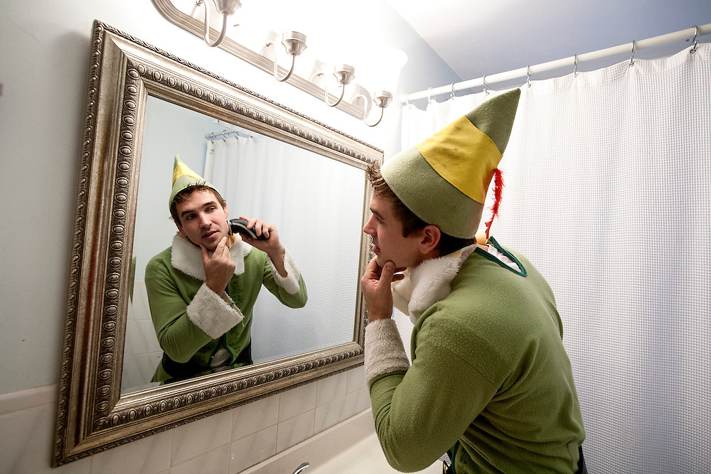 "Brandon Johnson, 29, shaves in preparation to work for his seasonal business, Santa's Tree Delivery, at his home in Northeast Minneapolis December 12, 2014.  ""Elves can't have stubble,"" he said."