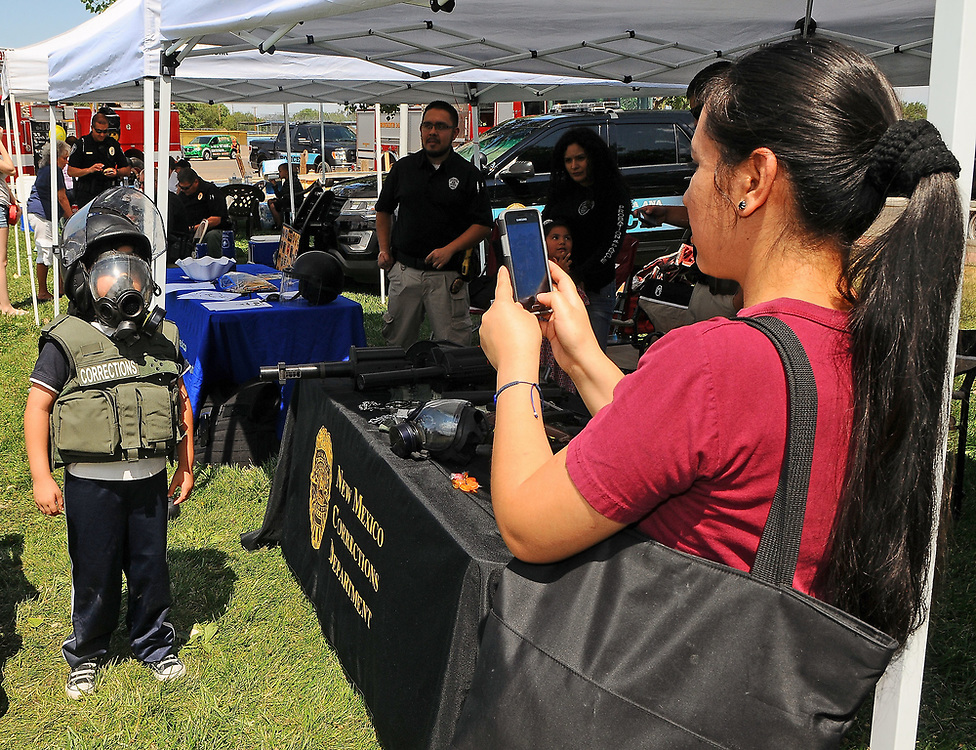 jt071417e/ a sec/jim thompson/Rafaela Alvarez takes a picture of her son Ricardo in a vest and helmet at the New Mexico Corrections Department booth at Rotary Park in Bernalillo,NM  as they attend the Cops in the Park celebration. Friday,  July. 14, 2017. (Jim Thompson/Albuquerque Journal)