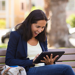 Stock Photo of Woman on Park Bench using Tablet Computer (Model Released)