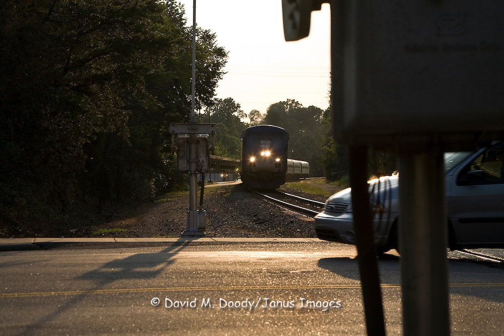 A car cutting it close as a train approaches the railroad crossing. Amtrak passenger train crossing on North Boundary St. Williamsburg, Virginia