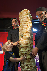 © licensed to London News Pictures. London, UK 20/07/2012. Cooks of Poppadom Restaurant and a 4 year-old Mia Mason posing with the World's Highest Poppadom Tower in Brady Arts and Community Centre. The 161cm tall tower managed to stand only 8 seconds but rules require 10 second to break the official world record. The record attempt was the part of the Curry Capital Festival in Brick Lane. Photo credit: Tolga Akmen/LNP