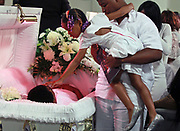 During the funeral for her father Demetrius Cooper and uncle LeAndre Cooper, 7-year-old Demiya Banks touches the head of her uncle while being held by LeAndre's son Leantae at New Beginnings Church on S. King Drive in Chicago on Saturday, Aug. 17, 2013. The brothers were shot and killed on August 6th in the West Pullman neighborhood.(Scott Strazzante/Chicago Tribune)<br /> ....OUTSIDE TRIBUNE CO.- NO MAGS,  NO SALES, NO INTERNET, NO TV, CHICAGO OUT, NO DIGITAL MANIPULATION...