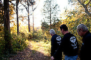 "Ghost hunters and cousins Andy and Chris Carter walk with Chris's father Grady through the woods after doing a follow-up investigation in a cotton gin that dates back to the 1830s. The ""paranormal investigators"" of Twisted Dixie are Grady Carter, Andy Carter, Chris Carter (all related), and Chris Phillips, seen in Antreville, South Carolina November 4, 2011."