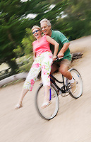 Woman riding on handlebars of mans bicycle