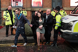 """© Licensed to London News Pictures . 24/12/2016 . Manchester , UK . Police intervene during a dispute and a woman is helped away . Revellers out in Manchester City Centre overnight during 2016's second """" Mad Friday """" , named for historically being one of the busiest nights of the year for the emergency services in the UK . Photo credit : Joel Goodman/LNP"""