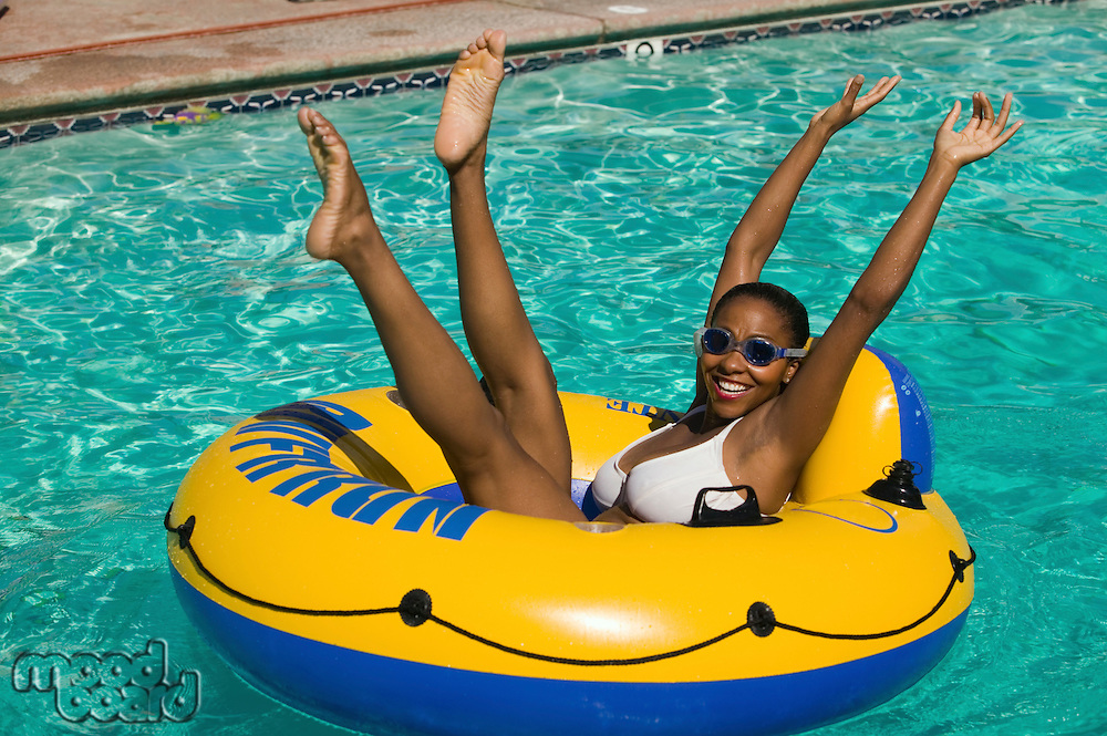 Woman Raising Arms and Legs in Pool Float