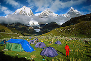 "Trekkers camp in a green pasture at 13,600 feet elevation in the Cordillera Huayhuash, Andes Mountains, Peru, South America. Yerupaja Grande (left, east face, 6635 m or 21,770 ft) is the second-highest peak in Peru, highest in Cordillera Huayhuash, and highest point in the Amazon River watershed. At center is Yerupaja Chico (20,080 feet). On right is Mount Jirishanca (""Icy Beak of the Hummingbird,"" 6126 m or 20,098 feet). Published up to 4 million copies in print and electronic media by Houghton Mifflin Harcourt (formerly Scholastic Inc) 2009-2034 for System 44 classroom paperback, ""Left to Die."" Published in ""Light Travel: Photography on the Go"" book by Tom Dempsey 2009, 2010."
