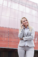 Beautiful young businesswoman using mobile phone while standing against office building