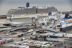 © Licensed to London News Pictures. 17/04/2020. Dover, UK. The Arcadia cruise ship (TOP) is berthed at Dover docks in Kent as freight traffic is loaded onto ferries. Europe's busiest port remains open with freight traffic continuing to run - but P&O have suspended all passenger services between Dover and Calais. The government have announced that lockdown will continue for another three weeks. The public have been told they can only leave their homes when absolutely essential, in an attempt to fight the spread of coronavirus COVID-19 disease. Photo credit: Peter Macdiarmid/LNP
