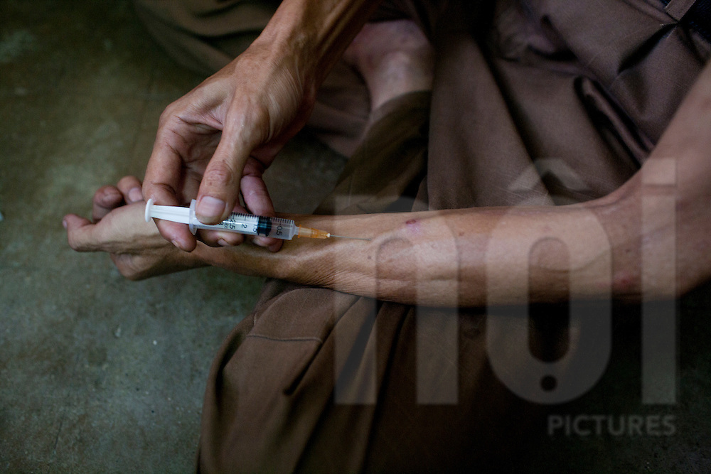 A man injecting drugs into his forearm in an old dormitory after recently returing from prison, Hanoi, Vietnam, Southeast Asia