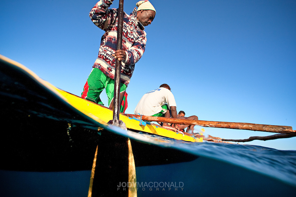 Two local fishermen in Madagascar search for octopus from their hand carved canoe near Anakao.  Capturing the scene from above and below the water gives the photo depth and interest.