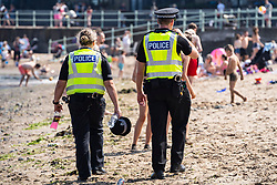 Edinburgh, Scotland, UK. 31 July, 2020. Temperature of 25C and sunshine brought  crowds to Portobello Beach outside Edinburgh. Several large groups of teenagers were enjoying beach and alcoholic drinks were very popular. Police start to confiscate alcoholic drinks