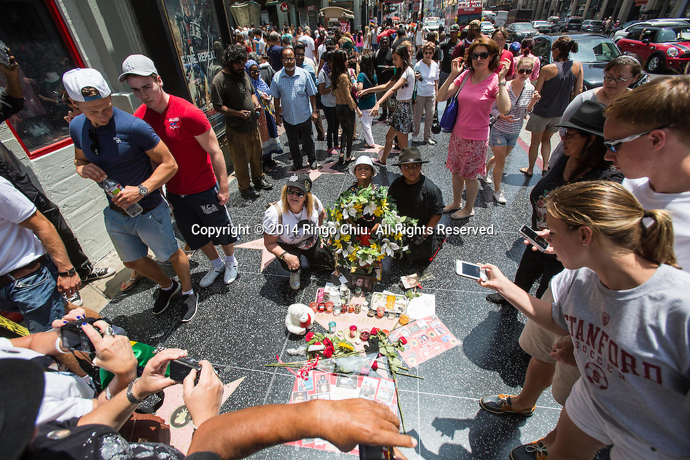 Fans of late pop star Michael Jackson pay tribute to his star on the Hollywood Walk of Fame near TCL Chinese Theatre to commemorate the 5th anniversary of his death on June 25, 2014 in Los Angeles, California. <br />  (Photo by Ringo Chiu/PHOTOFORMULA.com)