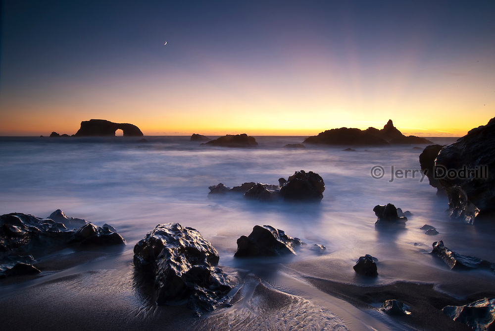 Twilight rays and crescent moon over Arched Rock at Blind Beach, Sonoma Coast State Park, California