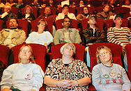 From left, foreground, Peggy Conners, 43, of Morrisville, PA., a 30 year smoker, Anne Minni, 43, of Bristol, PA., a 25 year smoker, and Minette Wijtyk, 35, of Bristol Borough, a 17 year smoker, sit and relax while attempting to be hypnotized at an AMC Movie Theater on Thursday, Nov. 19th, 1998, in Bensalem, PA.  Dr. Steven M. Rosenberg, not shown, tried to hypnotize about 500 people to never smoke again during the Great American Smokeout. (AP Photo/William Thomas Cain)