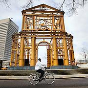 """Nederland Rotterdam 12 januari 2008 20080112 Foto: David Rozing ..Kunstwerk Delftsche Poort ( stadspoort ) een reconstructie in staal opgericht in 2005, ontworpen door de kunstenaar Cor Kraat naast Hofplein in het centrum van Rotterdam ...Piece of art """" Delftsche Poort """" Reconstruction of old city gate building in the centre of Rotterdam  ....?.De Delftsche Poort in Rotterdam was een stadspoort die in 1764 werd gebouwd naar een ontwerp van architect Pieter de Swart. Het was reeds de derde poort met die naam: de voorgaande twee waren wegens bouwvalligheid gesloopt. De eerste St. Joris- of Delftsche Poort werd in 1545 gebouwd..In de jaren '30 van de 20e eeuw stond de poort in de weg Men besloot de poort zo'n honderd meter te verplaatsen (afbreken stuitte op te veel weerstand). In 1939 begon men met de verplaatsing van het geheel. De onderbouw was in 1940 gereed, tijdens het bombardement werden zowel dit gedeelte als de opgeslagen beeldhouwwerken beschadigd. Een jaar later werd besloten dat """"naar het inzicht van de meerderheid van de geraadpleegde deskundigen de poort niet meer afgebouwd kon worden en moest zij geheel verdwijnen"""". Enkele sierwerken werden gered en opgenomen in de muren van de gebouwen op de hoek van het Stadhuisplein..Vijftig jaar later werd er op nagenoeg de oorspronkelijke plaats van de Delftsche poort aan het Pompenburg een reconstructie in staal opgericht, ontworpen door de kunstenaar Cor Kraat. Rond de poort zijn enkele restanten opgesteld van de gebeeldhouwde ornamenten die de oorspronkelijke poort sierden.....Foto: David Rozing/"""