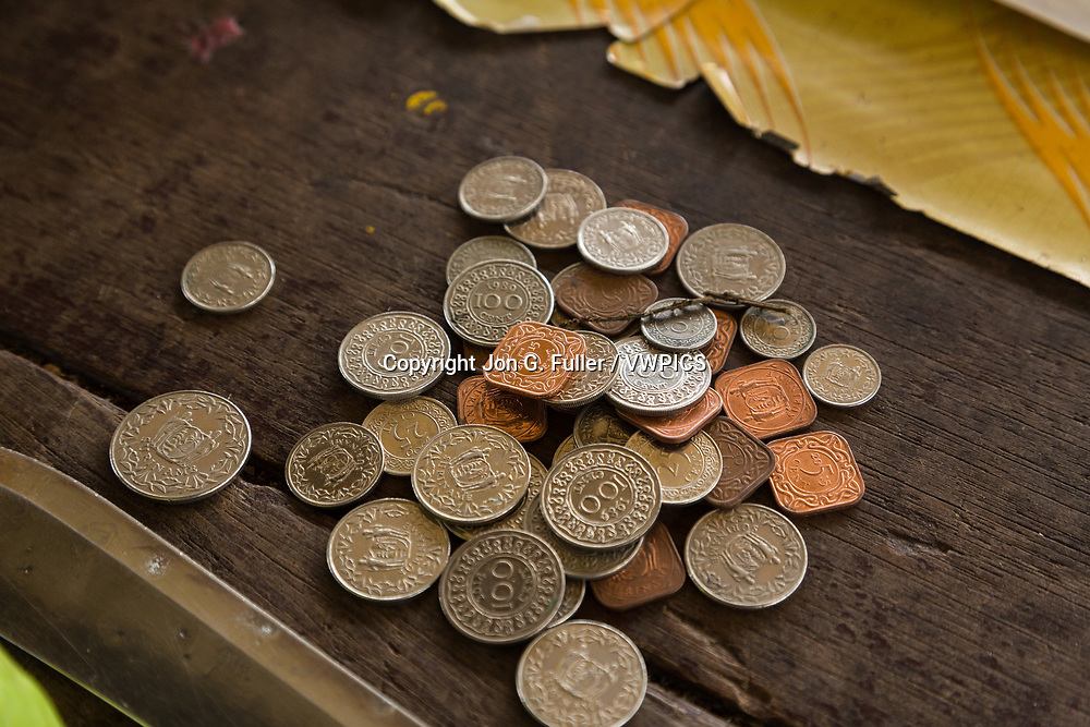 Surinamese coins on the counter top in a roadside market in Paramaribo, Suriname.